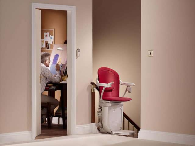 The Stannah 260 series Sofia red stairlift shown parked at the top of the stairs with the stair lift chair facing sideways to the stairs.