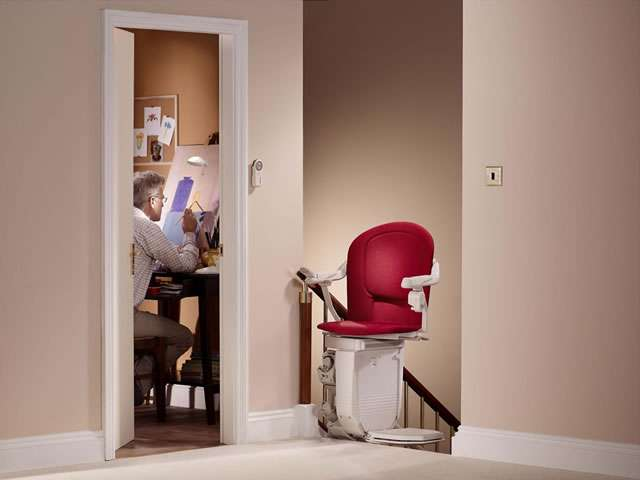 The Stannah 260 series Sofia red stairlift shown parked at the top of the stairs with the stair lift chair facing inwards to the landing. When the chair is positioned in this way, the stairlift acts as safety barrier.