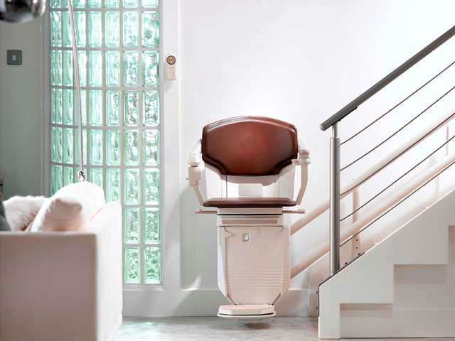 Front facing view of Stannah 260 series Solus curved stair lift in dark brown upholstery colour, parked at the bottom of the stairs.
