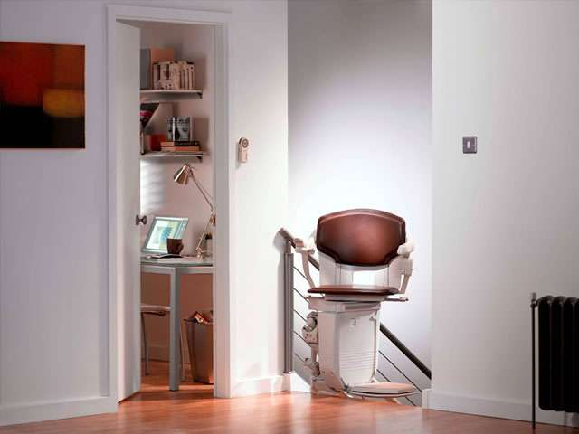 A Stannah 260 series Solus brown coloured upholstery stair lift shown parked at the top of the stairs with the chair facing inwards to the landing area. When the chair is positioned in this way, the chair helps provide a safety barrier at the top of the stairs.
