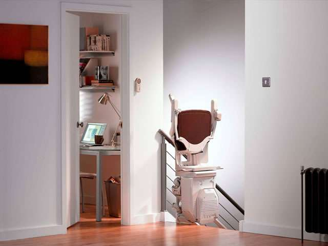 A Stannah 260 series Solus brown coloured upholstery stair lift shown parked at the top of the stairs with the chair facing sideways to the stairs, and the armresrs, seat, and footrest all set to the up position. When positioned like this, access to the stairs is made easier for people who do not need use of the stairlift.