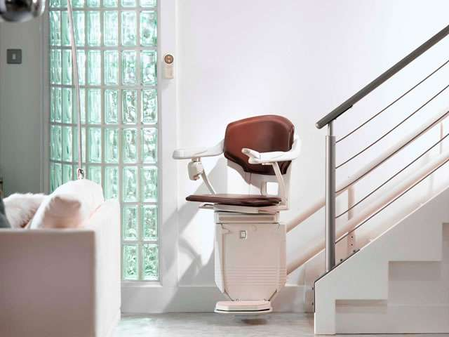 A near front facing view of the Stannah 260 series Solus stair lift situated at the bottom of the stairs, with armrests, seat, and footrest all in the down position.