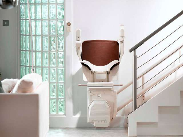 A full front facing view of the Stannah 260 series Solus stair lift situated at the bottom of the stairs, with armrests, seat, and footrest all in the up position.