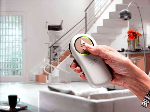 A close-up view of a user pressing the down button on the wireless remote control that is held in the hand and pointed toward the stairlift.