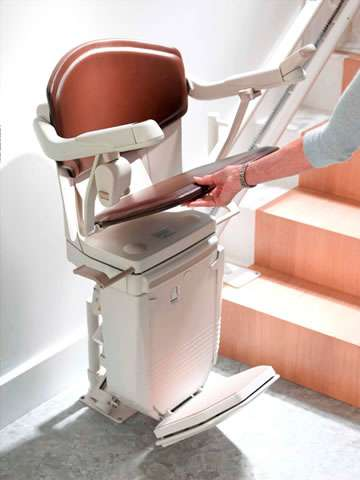 A female user lifting the seat of the Stannah 260 series Solus brown coloured stairlift. Because the arm rests and foot rest are linked internally to the chair seat, as the seat is moved upwards, the armrests and footrest also move up to match.