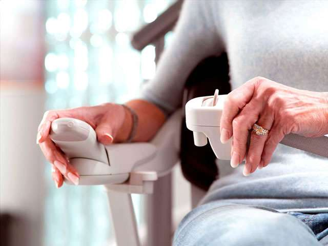 Close-up view of female user operating stairlift controls on Stannah 260 series Solus stair lift, and clasping the seatbelt closed.
