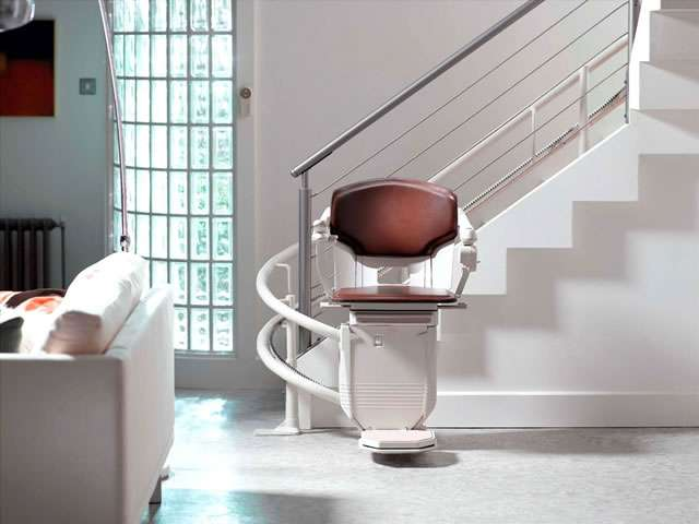 Front facing view of Stannah 260 series Solus stairlift in brown colour upholstery, parked at the bottom of the stairs, around a final curve, to ensure the the chair does not obstruct the stairs for people who do not need to use the stairlift.