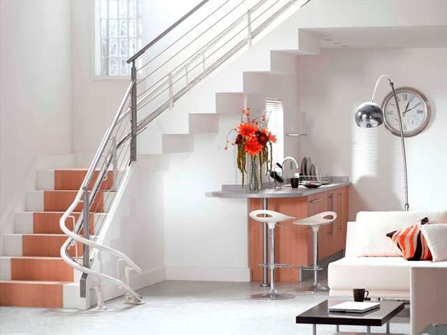 Showing the Stannah 260 series Solus stair lift curved rail that is installed near the bannister side opposite from the wall side.
