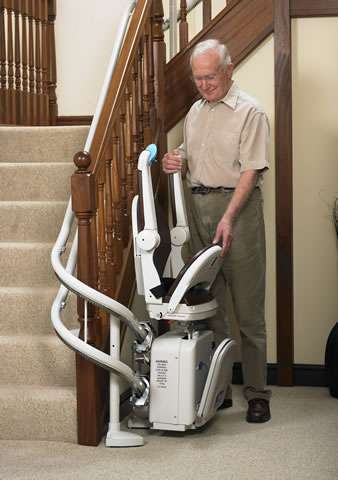 An elderly male user standing next to side view of Handicare 2000 brown coloured stair lift parked at the bottom of the stairs around a curve to keep the stairlift away from the stairs when not used. The user is moving the position of the Handicare 2000 arm rests and seat, while the footrest position is linked to the seat so follows its position.