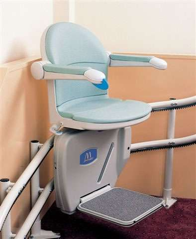 Handicare 2000 stair lift in light blue colour, situated on the curve of the stairs. Arm rest, seat, and foot rest all in the down position.