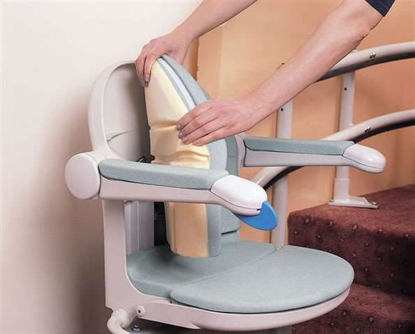 Close-up view of user's hands removing the light blue colour back chair padding on the Handicare 2000 stair lift.