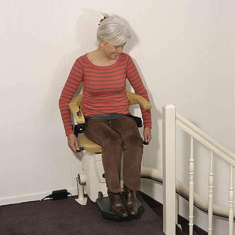 A smiling female user sat on a Handicare Van Gogh stair lift at the top of the stairs.