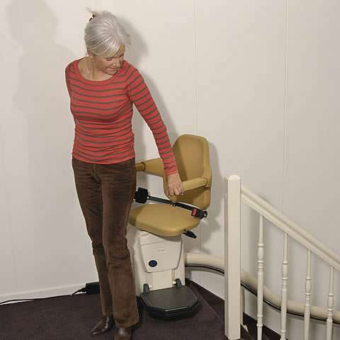 A smiling female user getting off a Handicare Van Gogh stair lift at the top of the stairs, facing the landing area.