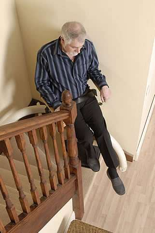An elderly male user sitting on a Handicare Van Gogh stair lift as it starts to travel up steep stairs.