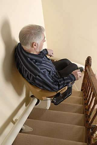 Looking from above, a mostly side view of an elderly male user sitting on a Handicare Van Gogh stair lift as it travels up steep stairs.