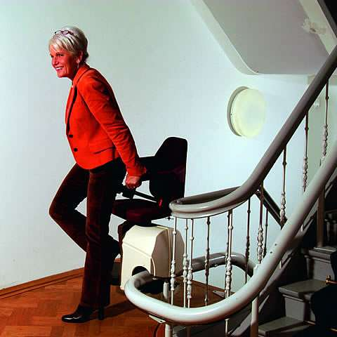 A smiling female user about to sit on Handicare Rembrandt stair lift chair on a middle stairs landing.
