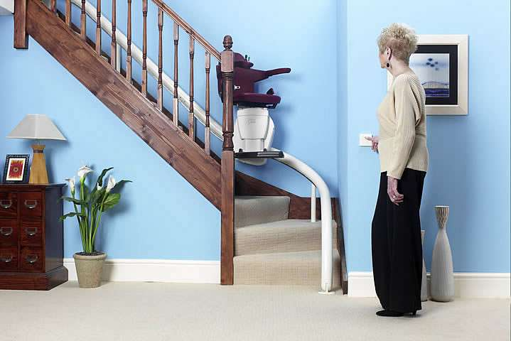 A female user standing at the bottom of the stairs operating the buttons on a wall-mounted remote control to bring the Handicare Van Gogh stairlift down the curved stairs.
