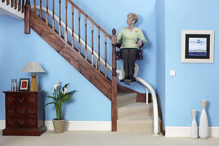 Female user sitting on a Handicare Van Gogh stair lift riding up the curved stairs.