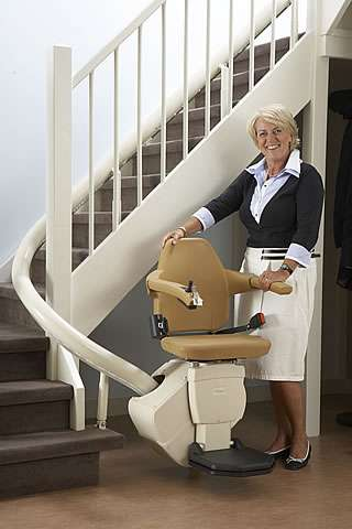 A female user standing next to a Handicare Rembrandt stair lift parked at the bottom of the stairs.