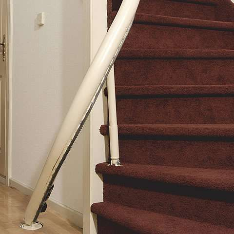 A photo that shows a Handicare stair lift rail that is fixed to steep stairs.