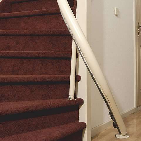 From the opposite side, a photo that shows a Handicare stair lift rail that is fixed to steep stairs.