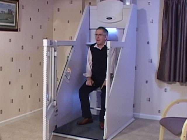 Male user sitting inside seat of a Wessex Lifts through floor home lift, with the access door open.