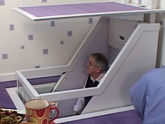 A side view of a male user sitting inside a Wessex Lifts through-floor home lift, about half-way down through the floor to the lower ground level.