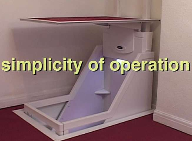 Shown from an angle view, a Wessex Lifts through floor home lift, travelling down the to floor below, with the phrase simplicity of operation printed on the image.