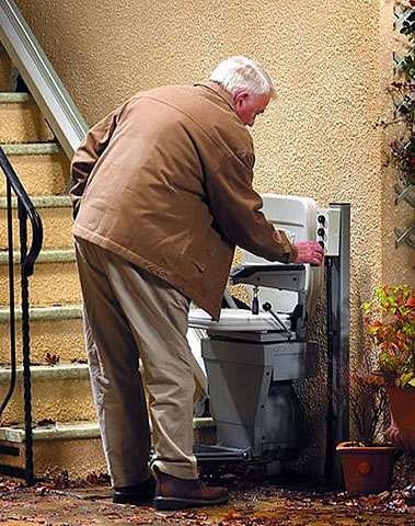 At the bottom of the external building steps, an elderly male user is pulling down the arm rest of the Stannah 320 outdoor stair lift.