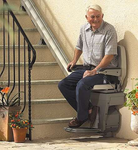 Smiling elderly male user sat on the Stannah 320 outdoor stair lift about the be transported up external straight stairs.