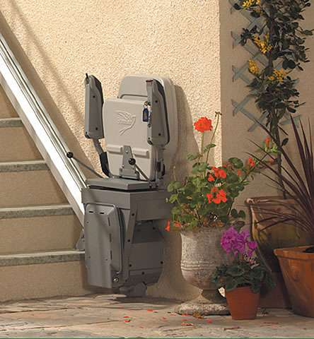 The Stannah 320 outdoor stair lift parked at the bottom of the external stairs outside. The seat, armrests, and footrest are all in the closed up position, allowing lots of space for people who do not require the use of the stair lift to go up and down the outside steps.